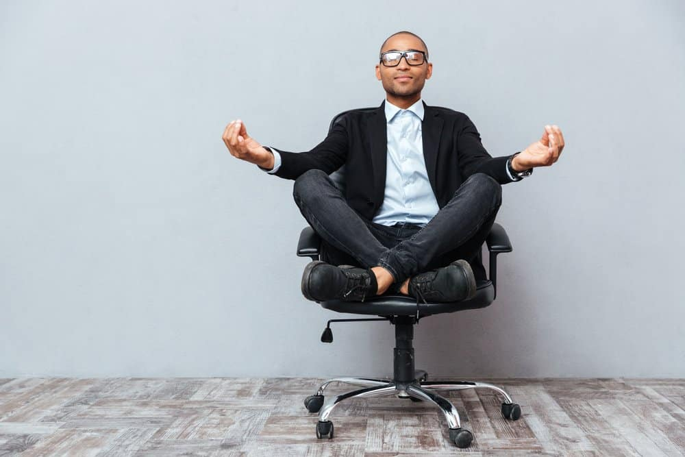 Man sitting with legs crossed in office chair with arms in yoga pose.