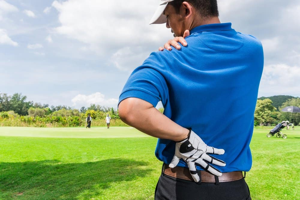 Golfer on golf course holding left shoulder and lower back in pain.