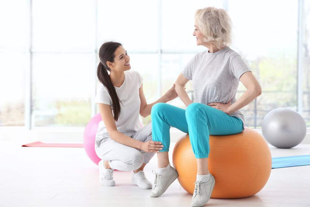 Older woman sitting on balance ball working with professional.