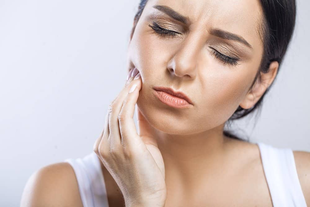 Woman rubbing jaw in pain.