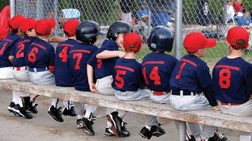 Little league baseball team sitting on bench during game.