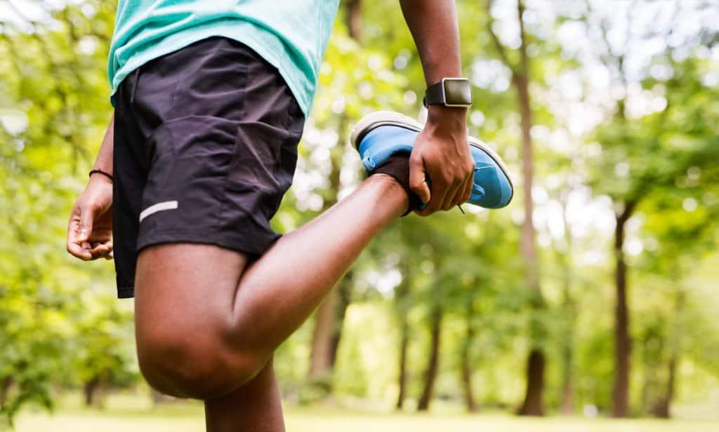 Runner in park stretching leg.