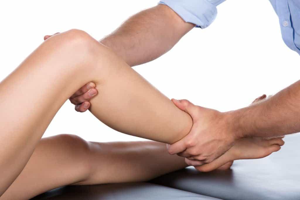Professional manipulating right leg of patient.