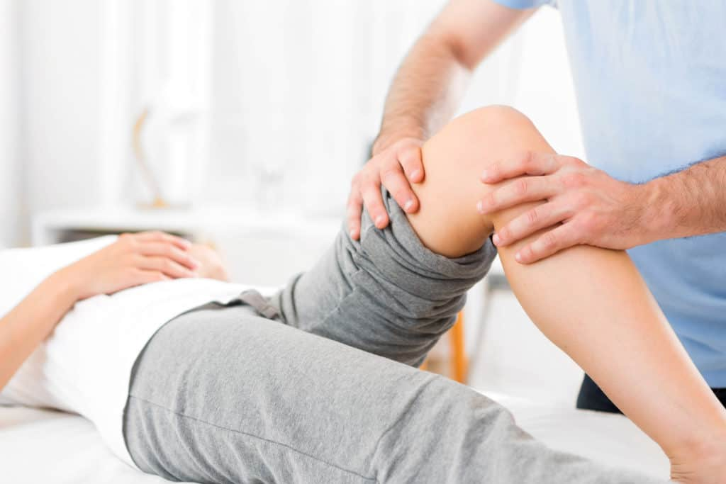 Physical therapist with hands on knee area of patient.