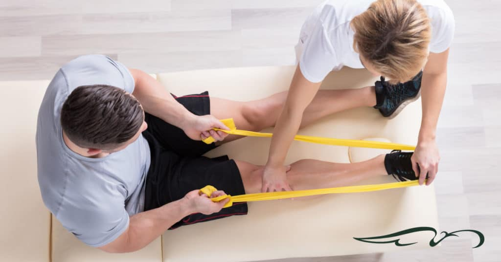 Man working with rubber bands and physical therapist.