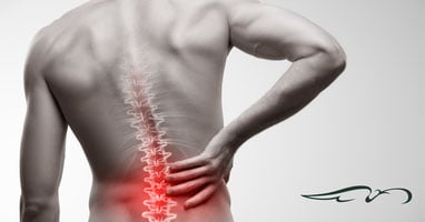 Man grabbing lower back showing red around spine