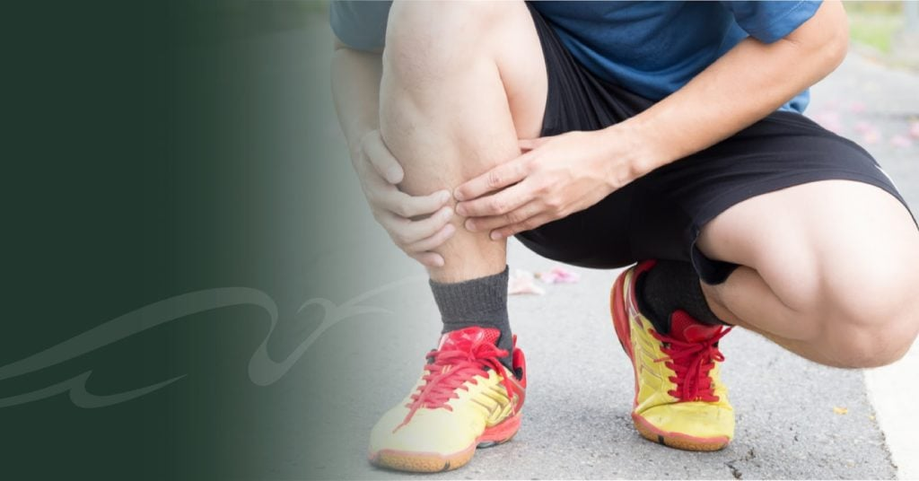 Man in running clothes holding his shin for a blog post about shin splints.